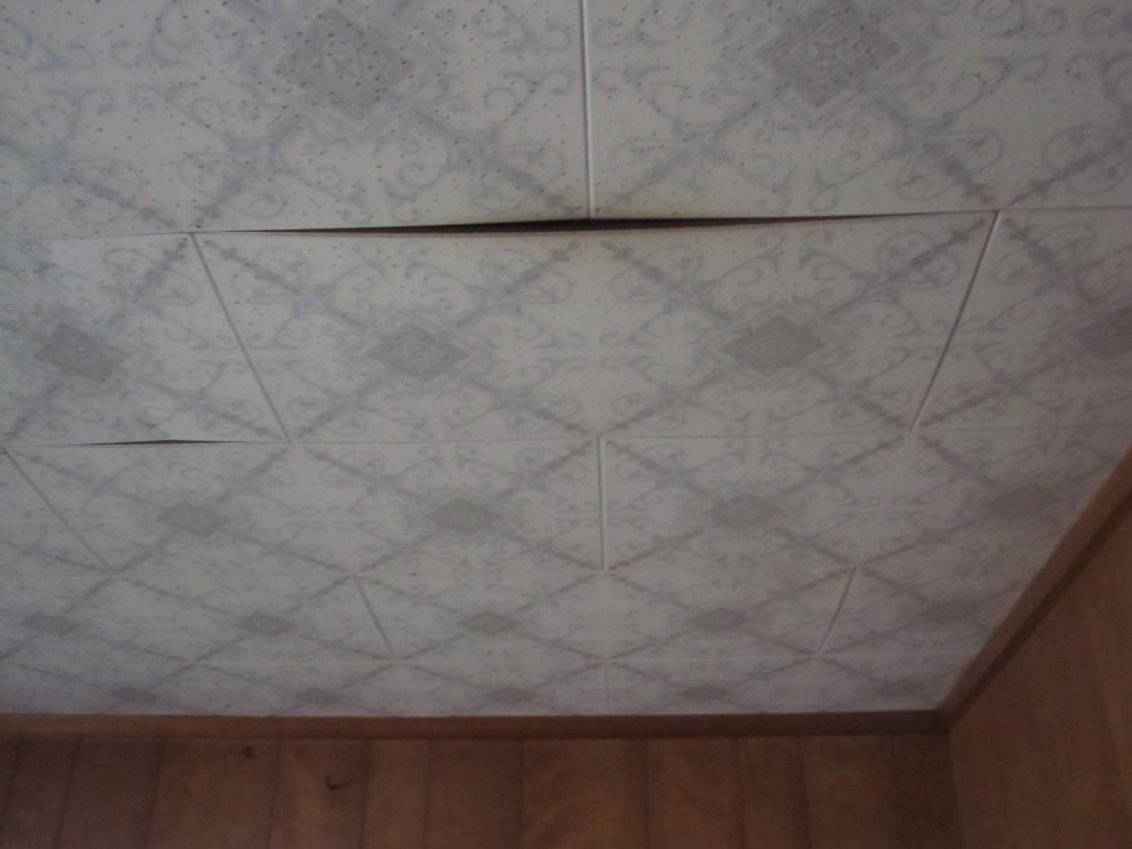 天井の壁が曲がって剥げた様子
