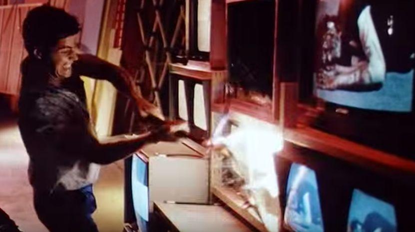 必死にテレビ画面を叩き割る男性