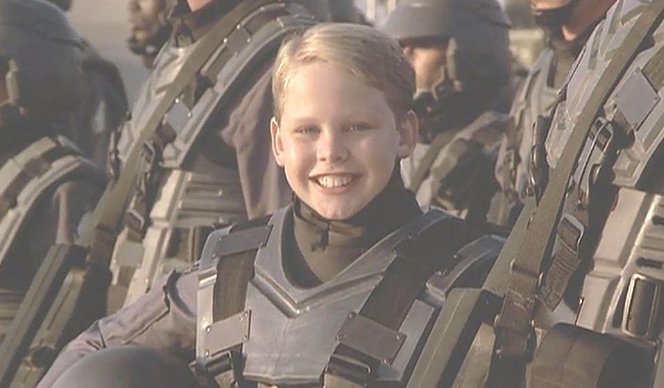 まだあどけない表情の少年が兵士の格好をしているシーン