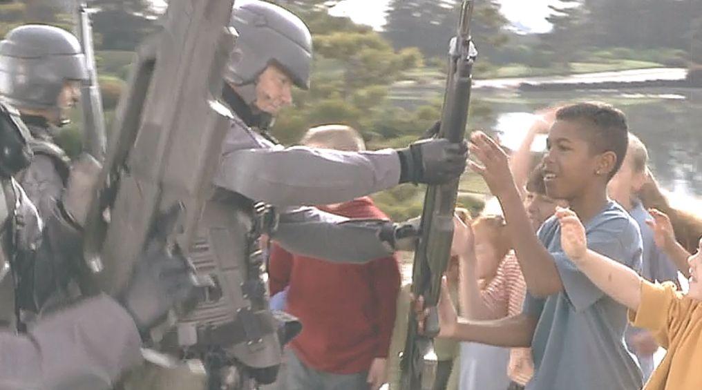 兵隊が子どもたちに銃器を手渡すシーン