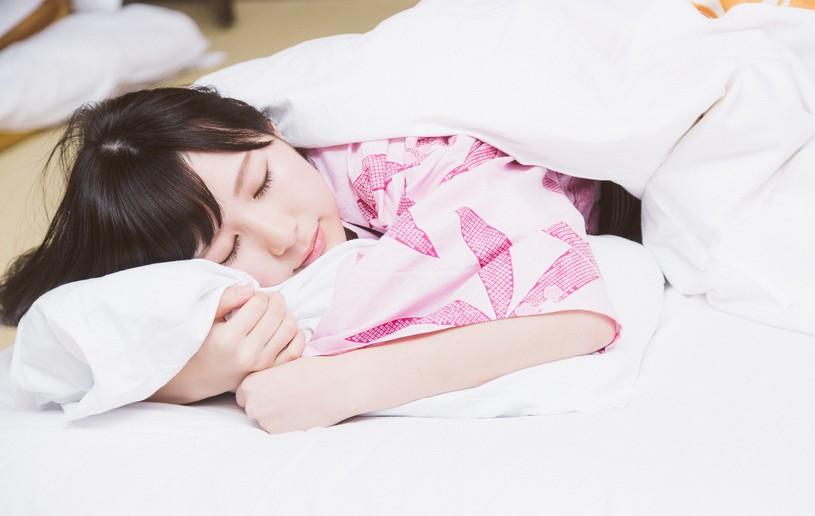 自分の腕を枕に寝る女性