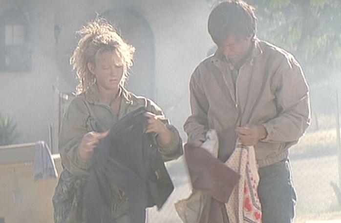 灰燼と化した住まいで踏み荒らされた衣服を拾い集める人々