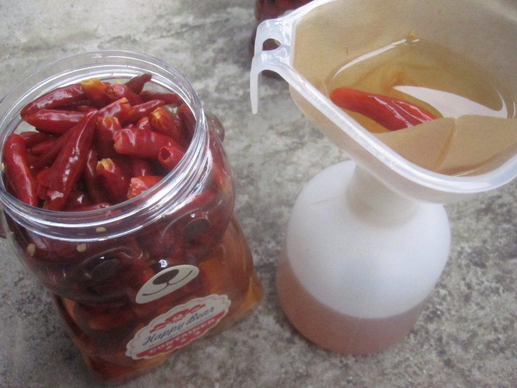 自家製の殺虫剤「唐辛子&ニンニクの酢漬け」をスプレー容器に移す作業中