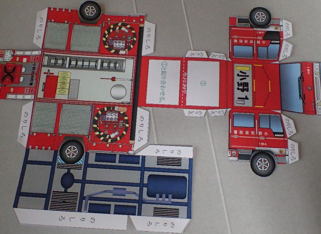 消防車のペーパークラフトを切って貼って組み立てる様子